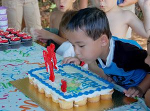 Image of a young boy blowing out the candles on his birthday cake at a waterpark party
