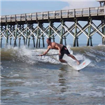 Man SUP surfing on Folly Beach