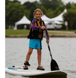 Young girl on a stand up paddleboard on the the lake at James Island County Park