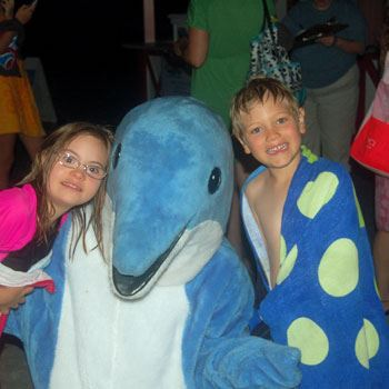 Two kids and mascot Daphne the Dolphin at Special Needs Swim Night