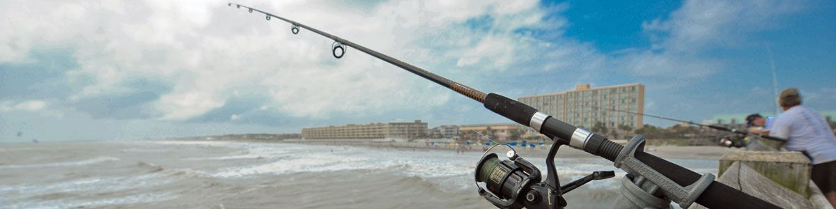 Image of a fishing rod on the Folly Beach Pier with the Atlantic Ocean in the background