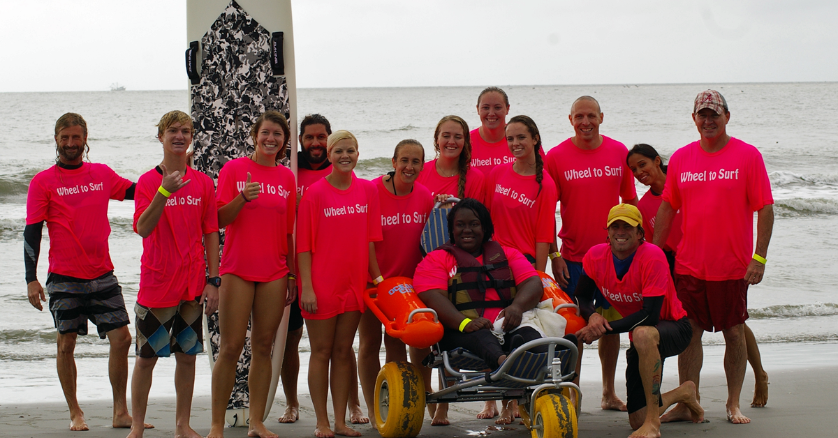 Image of a Wheel to Surf Adaptive Surfing participant and volunteers on the beach