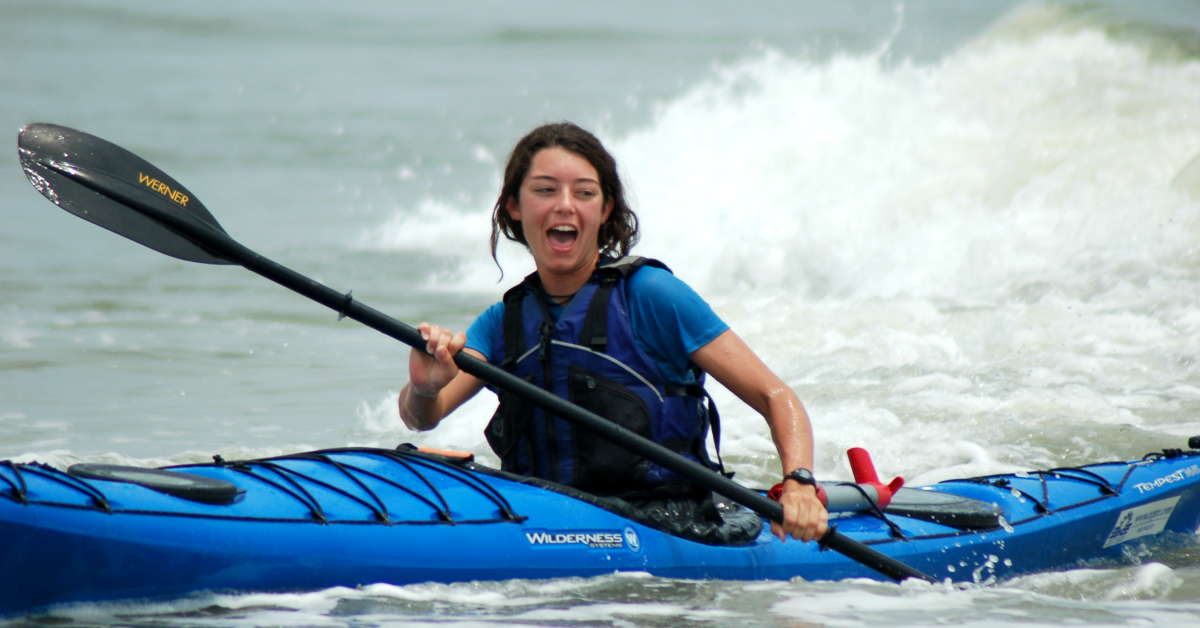 Image of a woman paddling a Kayak in the ocean
