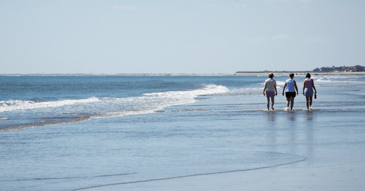 Three women walking along the surf at Kiawah Beachwalker Park