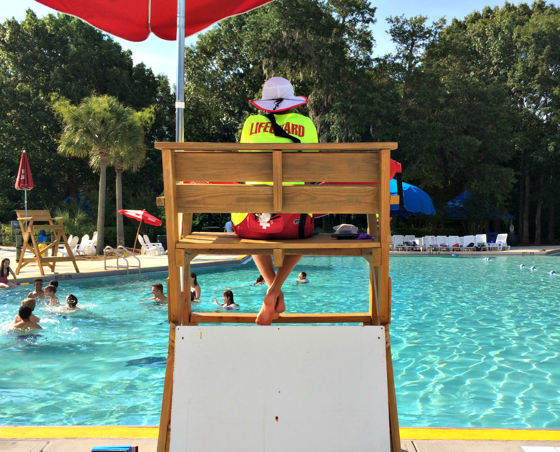 Waterpark lifeguard in a stand overlooking a pool with people swimming