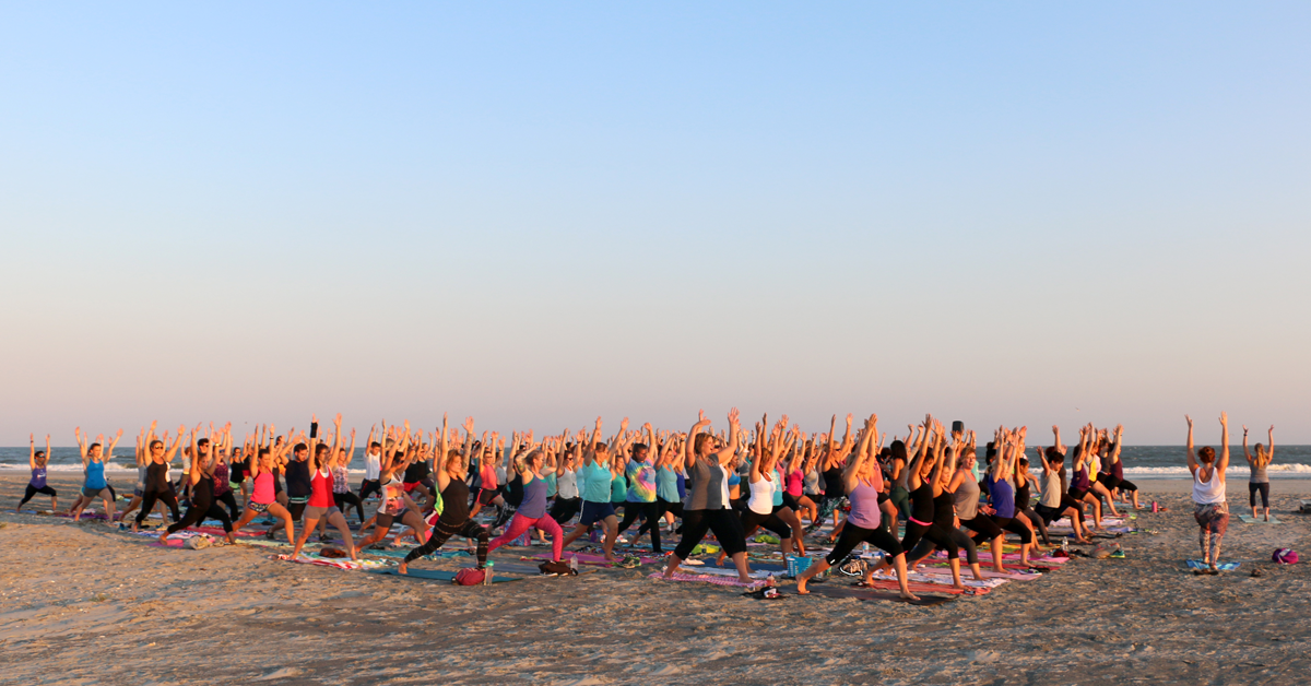 Over two hundred people practicing yoga on the beach at sunset