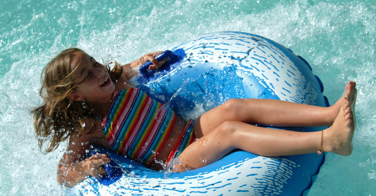 Young girl riding on an innertube at the waterpark