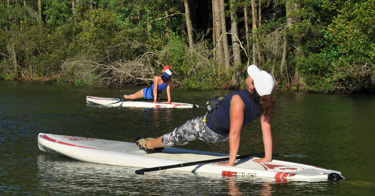 Two women practicing yoga on stand up paddleboards on the lake at James Island County Park