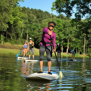 SUP Fitness participants paddling stand up paddleboards on the lake at James Island County Park