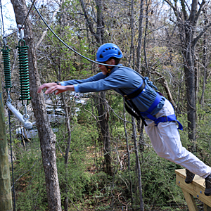 Man leaping from a wood deck to a swing during the Leap-of-Faith challenge on the Challenge Course