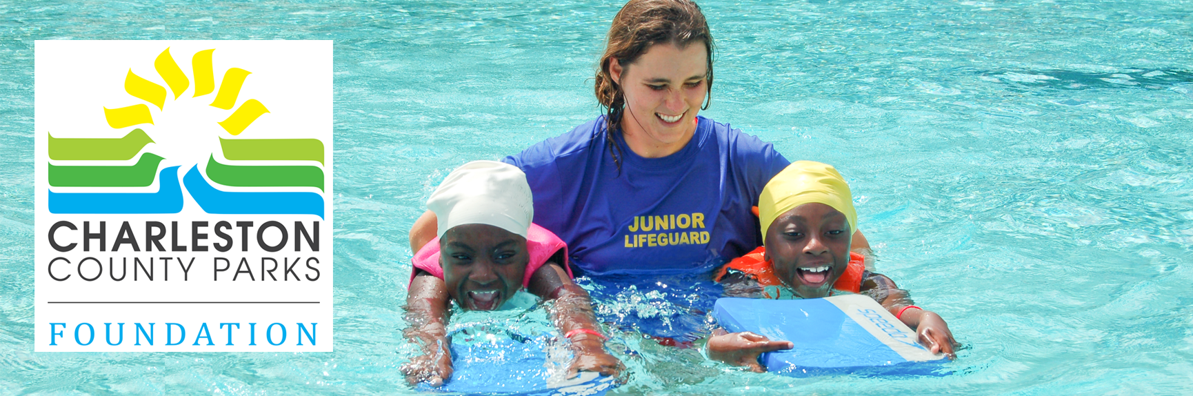 A swim instructor teaching two girls how to swim