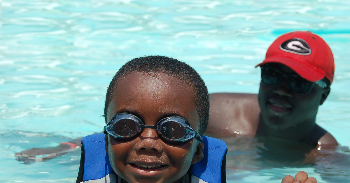 A child in swim goggles and a man in a hat in the pool