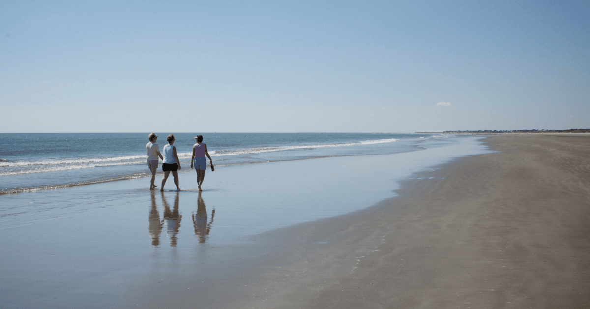 Three women walking along the beach