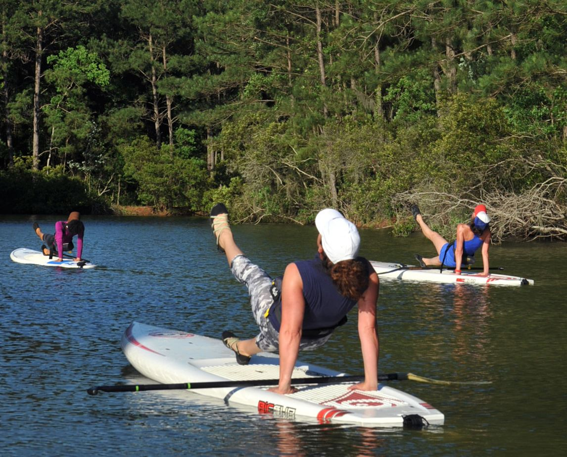 Three women practicing SUP yoga on a stand up paddleboard on the water