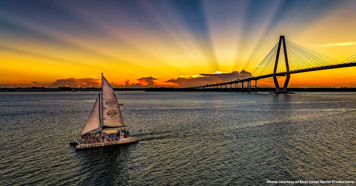 The Palmetto Breeze Catamaran cruising on Charleston harbor at sunset - Photo courtesy of East Coast