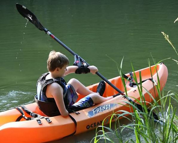Child in kayak with adaptive paddle