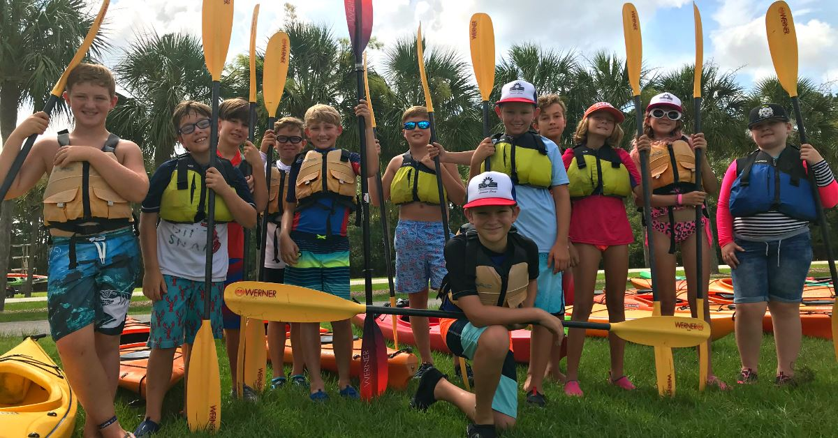Summer camp kids holding paddles