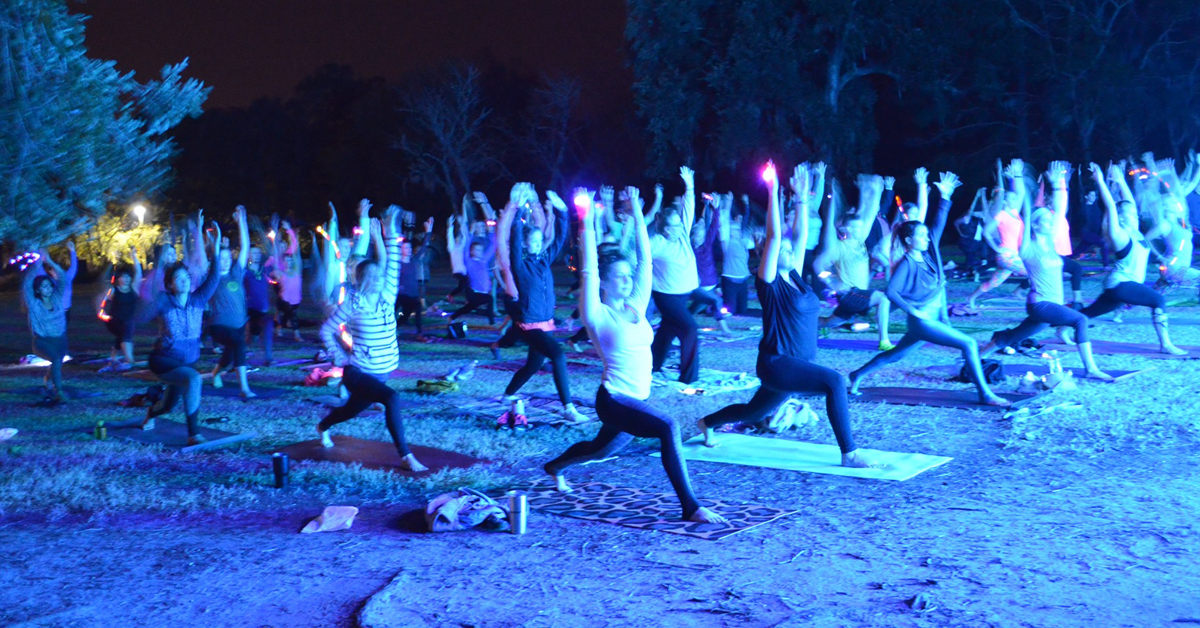 People practicing yoga at night at Holiday Festival of Lights