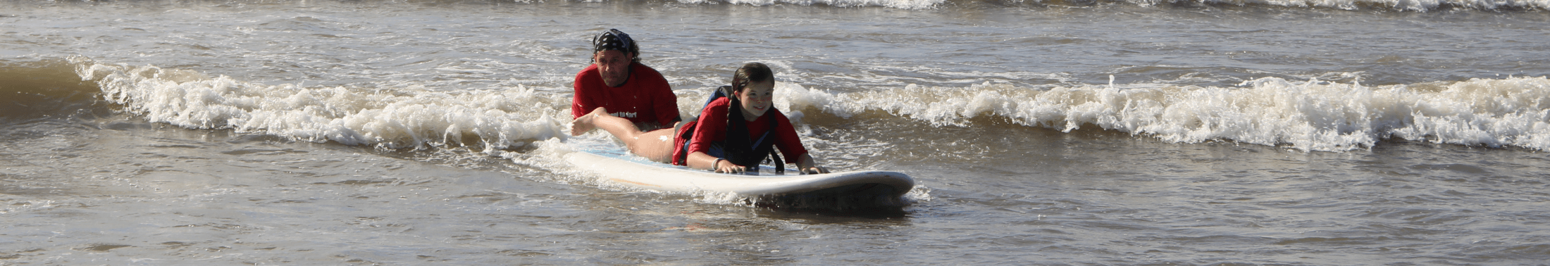 Man helps little girl learn to surf