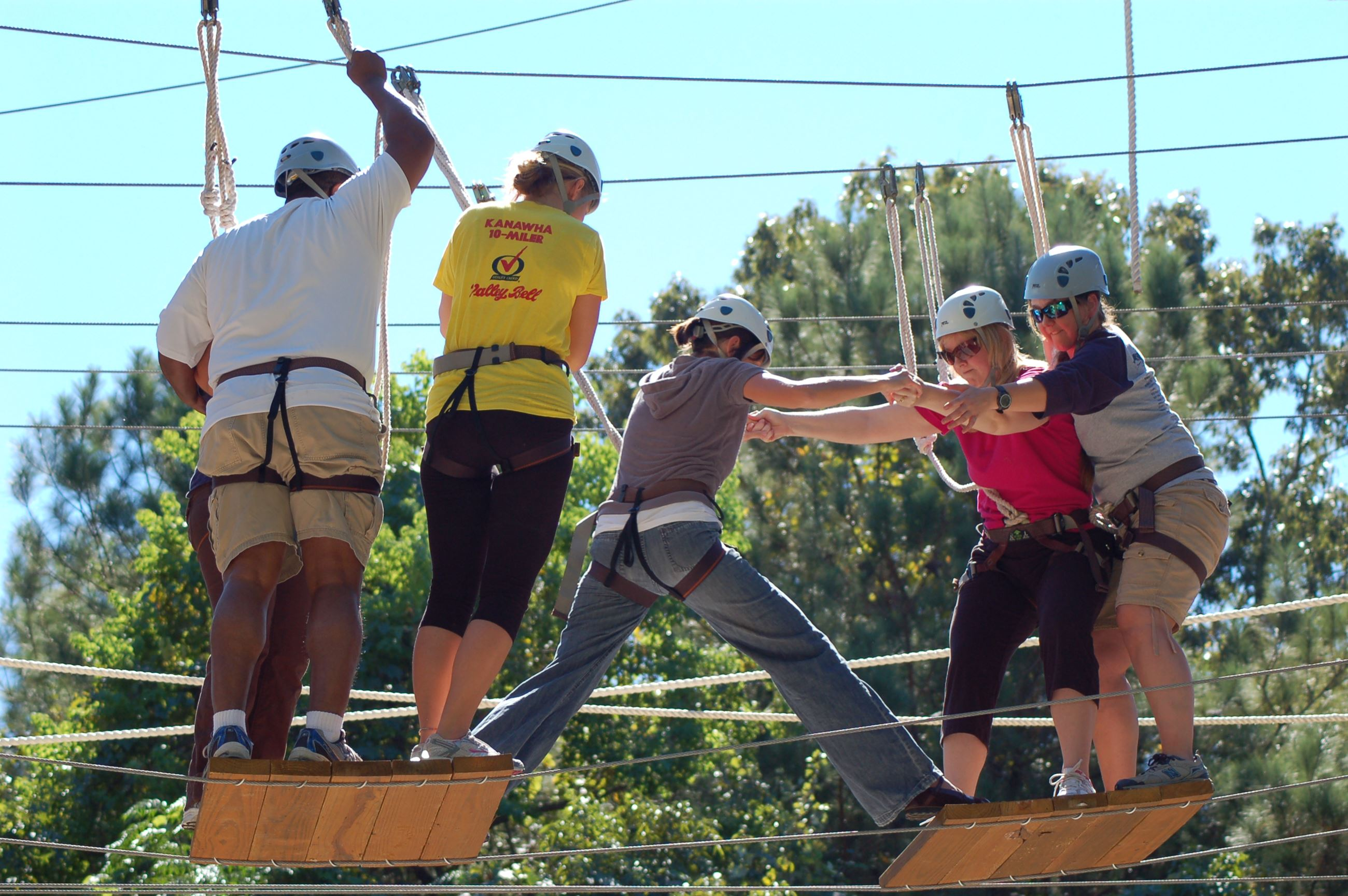 Group of people help each other on the high ropes course