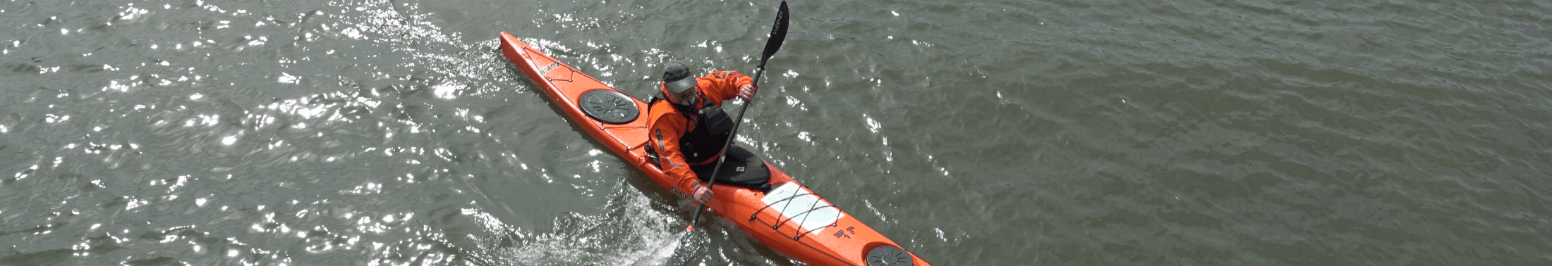 Man kayaks in open water