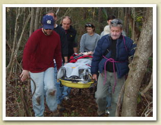 Group carrying a gurney through the woods.