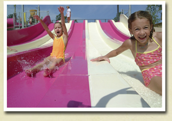 Little girl sliding down a water slide