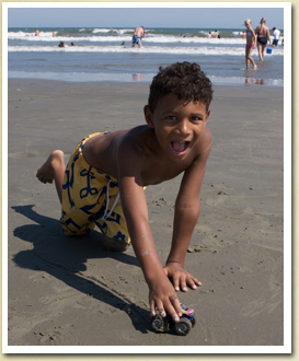 A little boy plays with a truck on the beach