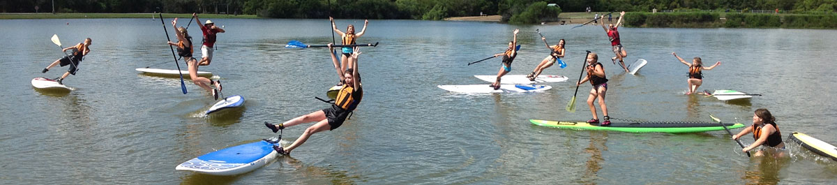 Summer campers jumping off stand up paddleboards at James Island County Park