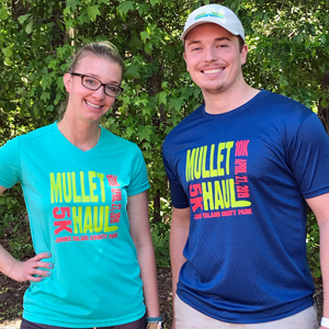 A woman and a man wearing the Mullet Haul race shirts