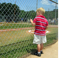 Young boy looking through a chain link fence on to a baseball field