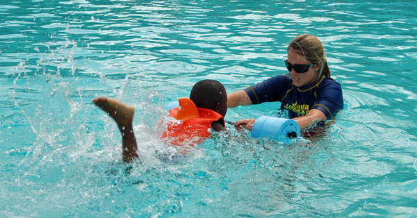 Swim instructor teaching a young child how to swim