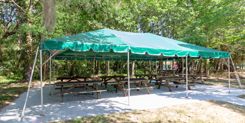 Funyard-Tent - green and white striped tent with picnic tables underneath