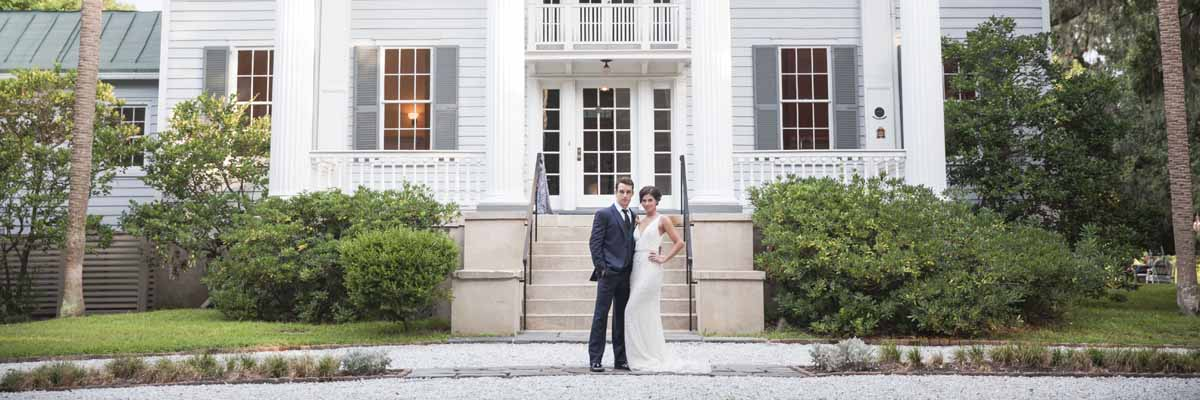 Image of a bride and grrom in front of the main house at McLeod Plantation Historic Site