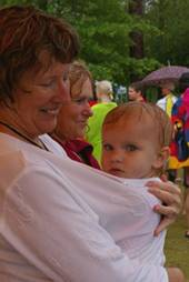 A woman holds a wet baby in her shirt